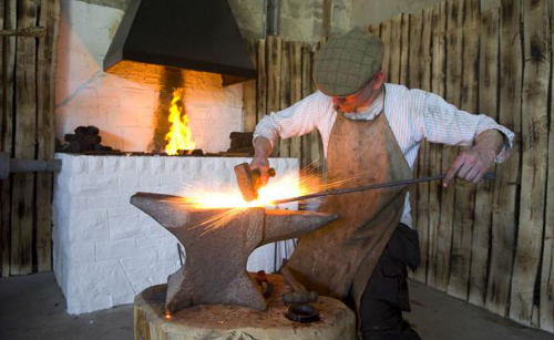 [Photo of a blacksmith at work]
