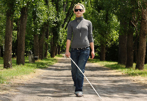 [Photo of a young blind woman walking in the woods]