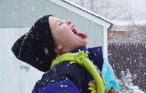 [Photo of a boy letting snow fall onto his tongue]