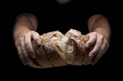 [Photo of a person breaking a loaf of bread]