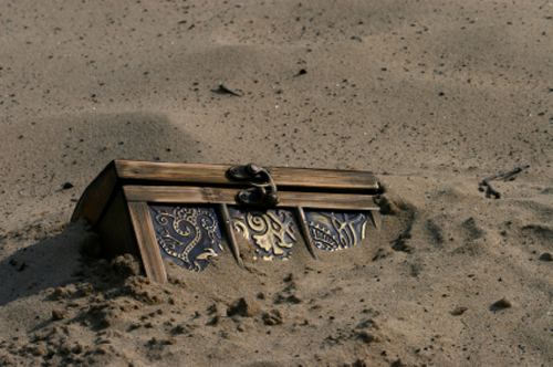 [Photo of a partially buried treasure chest]