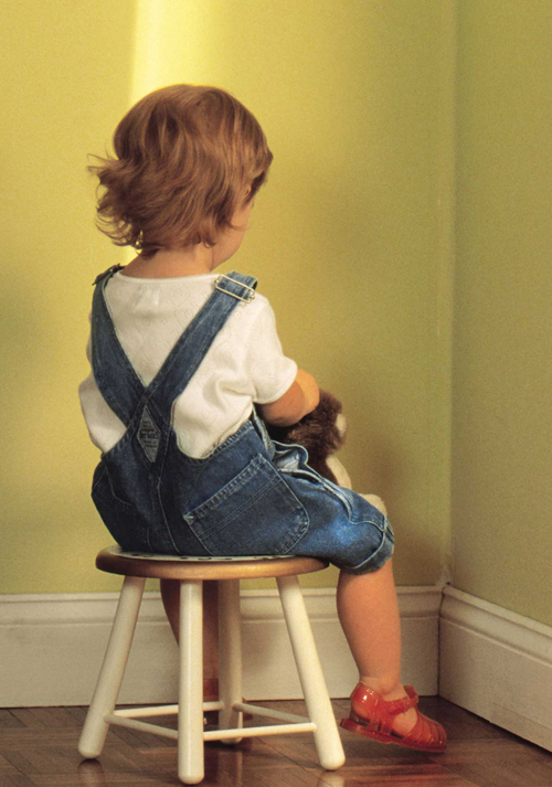 [Photo of a child sitting in a corner]