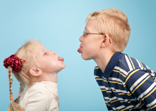 [Photo of two children sticking out their tongues at each other]
