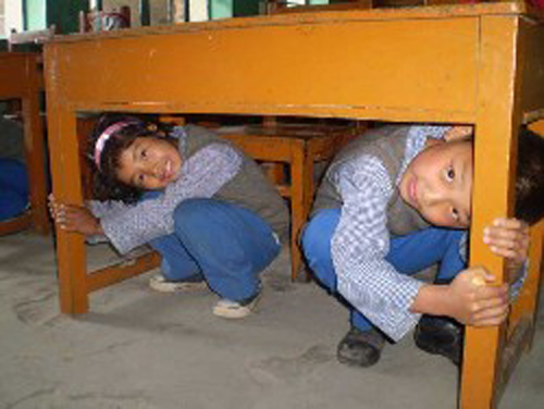 [Photo of children hiding under a table]