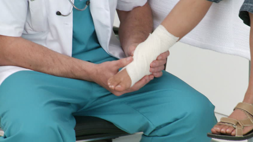 [Photo of a doctor examining a foot]