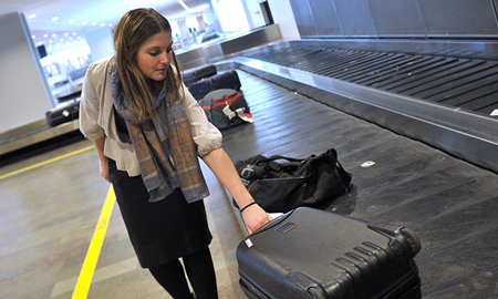 [Photo of a young woman getting her luggage at an airport]
