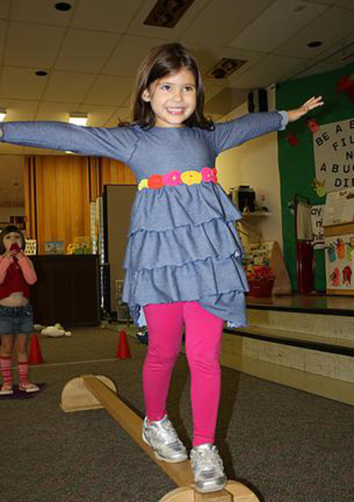 [Photo of a little girl on a balance beam]