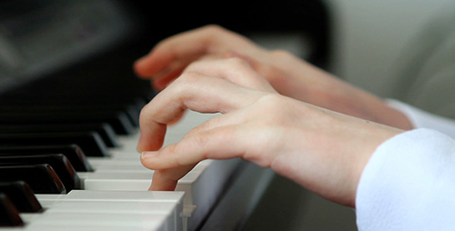 [Photo of a woman's hands on a piano]