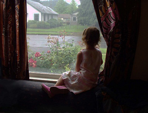 [Photo of a little girls looking out a window]