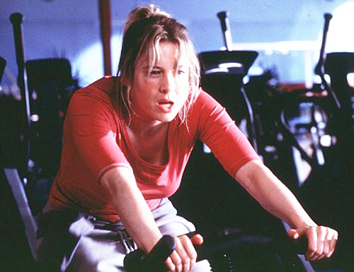 [Photo of a woman riding an exercise bike]