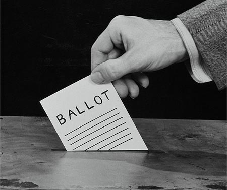 [Photo of placing ballot into a ballot box]