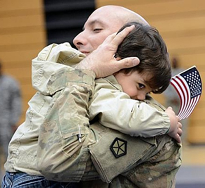 [Photo of a little boy welcoming his soldier father]