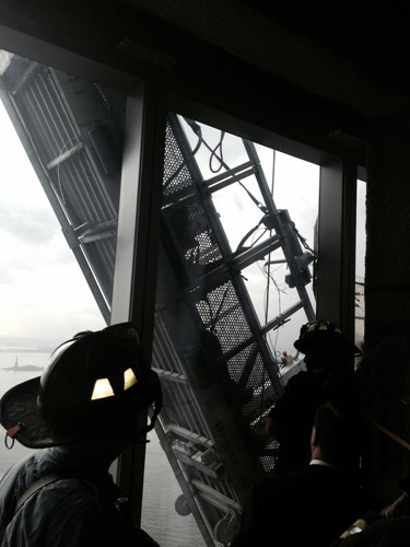 [Photo of fire department personnel rescuing trapped window washers]