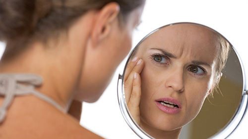 [Photo of a woman examining her face in a mirror]
