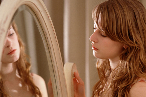 [Photo of a young woman looking into a mirror]