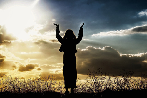 [Photo of a woman raising her arms in praise]