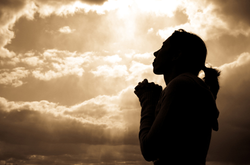 [Photo of a woman in silhouetter praying]