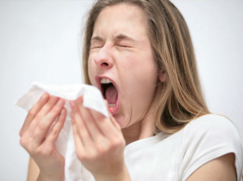 [Photo of a woman sneezing]