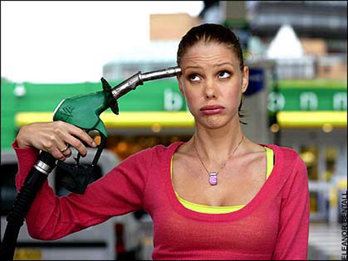 [Photo of a woman holding a fuel nozzle ot her head]