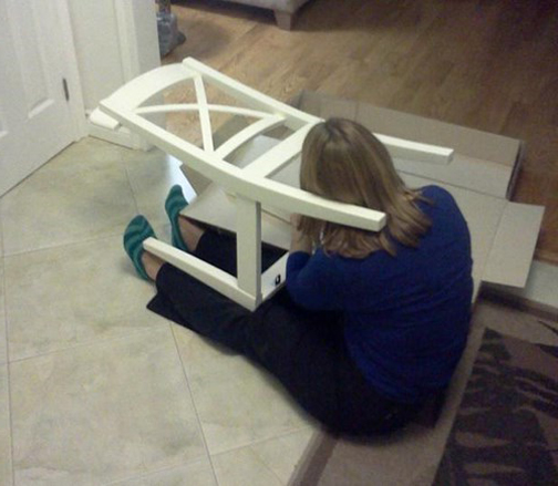 [Photo of a woman struggling to assemble a chair]