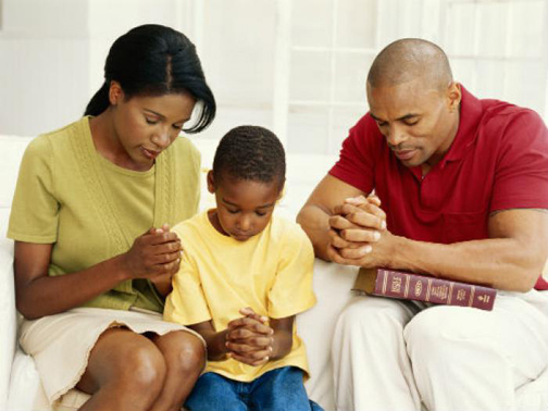 [Photo of a family praying]