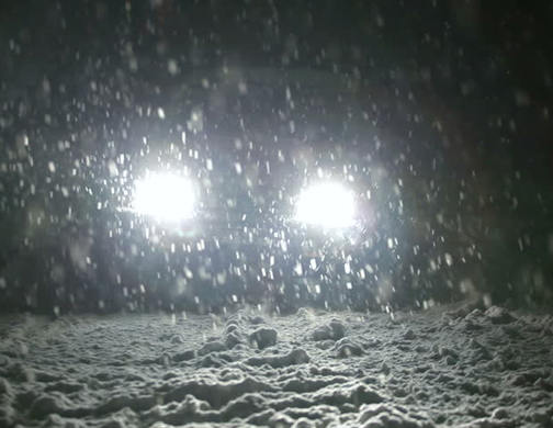 [Photo of headlights in falling snow]