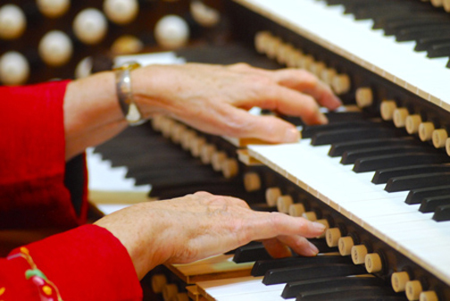 [Photo of an organist's hands on the organ keyboard]