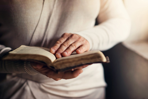 [Photo of a woman holding a Bible]