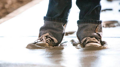 [Photo of two sneaker feet stuck in concrete]